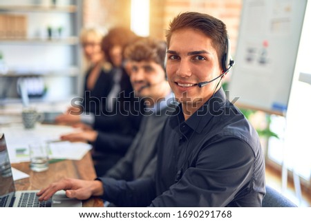 Group of call center workers working together with smile on face using headset. Young handsome man smiling at the office. #1690291768