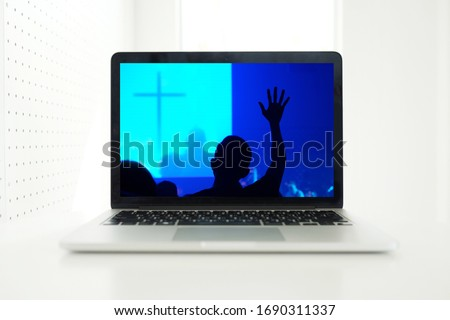 Church services online concept, Home church during quarantine coronavirus Covid-19, Online church from home new normal concept, Cross with worship hand in screen laptop, spirituality and religion. #1690311337