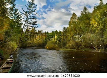Far east wild forest river. Autumn red and yellow color foliage falls and fly by wind over the taiga river. Old hunter boat attached near the forest shore. Bright sunny day landscape #1690351030