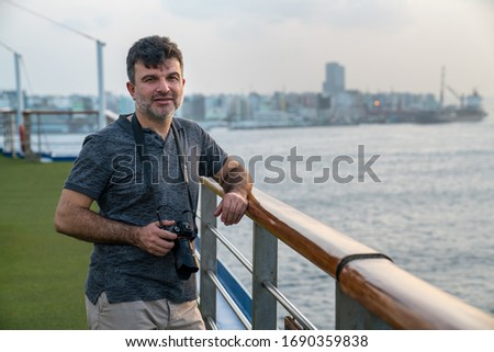 Man taking pictures on cruise ship on tourist trip