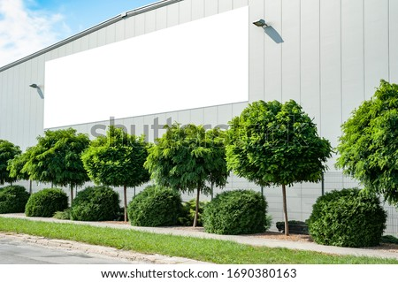 Blank white billboard for advertisement mounted on the wall of warehouse/factory