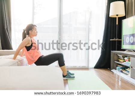 Video streaming Stay home.home fitness workout class live streaming online.Asian woman doing strength training cardio aerobic dance exercises watching videos in the living room at home.Covid-19. #1690397983