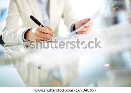 Hands of young businesswoman signing paper