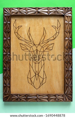 Wooden picture with the image of a deer made using the technique of pyrography and decorated with a carved frame