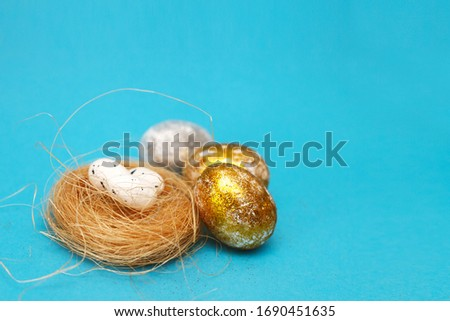Gold and silver Easter eggs on a blue background. Easter concept. Front view. Copy space #1690451635