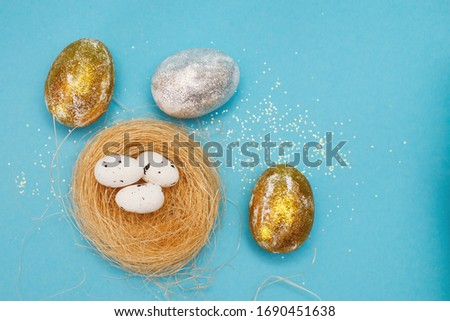 Gold and silver Easter eggs on a blue background. Easter concept. Front view. Copy space #1690451638