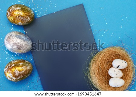 Gold and silver Easter eggs on a blue background. Easter concept. Front view. Copy space #1690451647