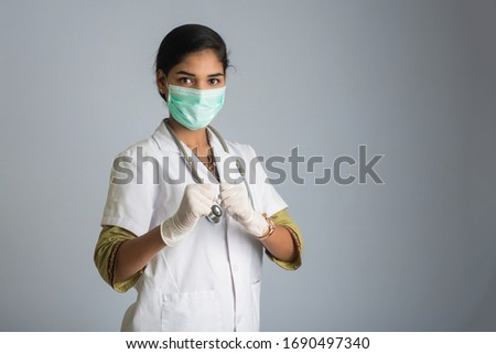 Young woman doctor wearing medical face mask Showing sign. Doctor woman wearing surgical mask for corona virus. #1690497340