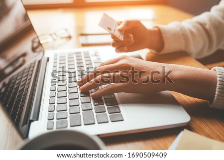 A young woman makes an online payment for a purchase. Online shopping. Royalty-Free Stock Photo #1690509409