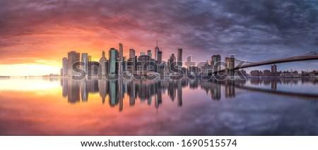 New york skyline reflection on the Hudson river at Brooklyn bridge at sunset Royalty-Free Stock Photo #1690515574