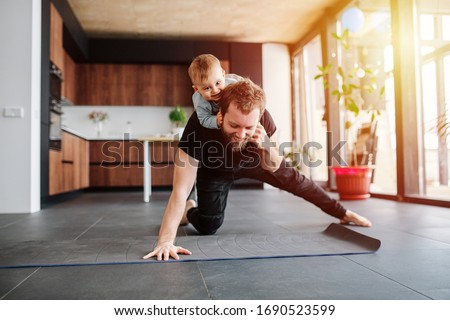 Father working out, doing single arm plank with his jolly infant baby riding on his neck. Stay at home apartment. Family quarantine, domestic life in self-isolation. Sunset light  #1690523599