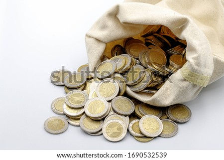 Business and financial, Saving money concept, Multi Euro coins (1€ and 2 € EUR) poured from a bag on a white background, Stack of metal coins in raw cotton bag, Eurozone currency exchange. #1690532539