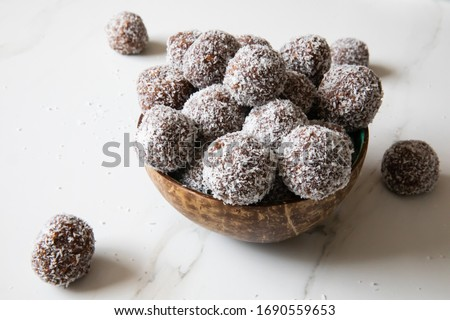 Delicious Coconut-Chocolate balls covered with grated coconut served in a coconut plate against white background. Copy space. Christmas, Indian burfi treat, healthy energising cookie concept  Royalty-Free Stock Photo #1690559653