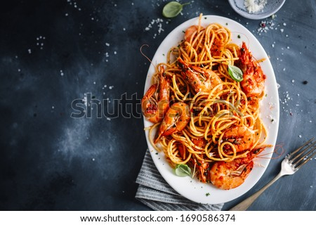 Pasta spaghetti with shrimps and tomato sauce served on plate on dark background.  #1690586374