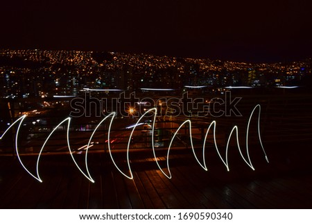 Long exposure photography with light painting technique, forming waves and city lights in the background. La Paz, Bolivia