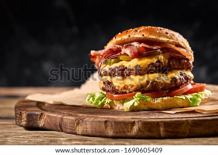 Juicy American burger, hamburger or cheeseburger with two beef patties, with sauce and basked on a black background. Concept of American fast food. Copy space Royalty-Free Stock Photo #1690605409