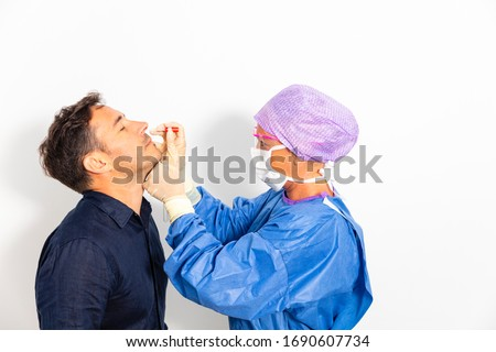 A doctor in a protective suit taking a nasal swab from a person to test for possible coronavirus infection Royalty-Free Stock Photo #1690607734