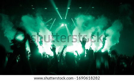 Happy people dance in nightclub DJ party concert and listen to electronic dancing music from DJ on the stage. Silhouette cheerful crowd celebrate New Year party 2020. People lifestyle DJ nightlife. #1690618282