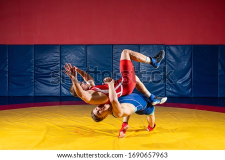 Two  strong men in blue and red wrestling tights are wrestlng and making a suplex wrestling on a yellow wrestling carpet in the gym. Wrestlers doing grapple.  #1690657963