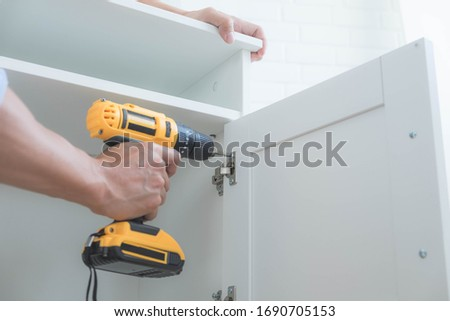 The mechanic assembled the furniture in the house according to the manual, along with the mechanic equipment. By hammering the nails Measuring with a tape measure Screwing the screw Drilling holes. #1690705153