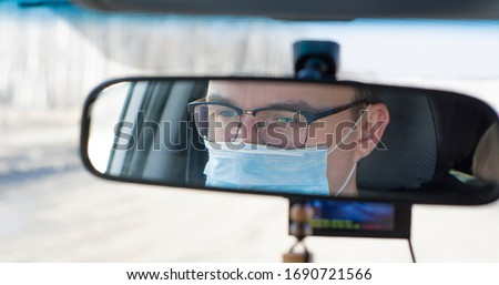 Coronavirus. A young male driver is sitting in a car wearing a medical mask. view of the rear view mirror of the car. self-defense against the virus #1690721566