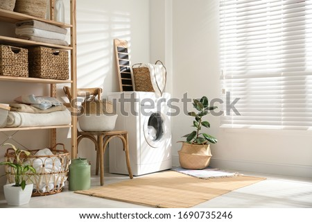 Modern washing machine and plants in laundry room interior #1690735246