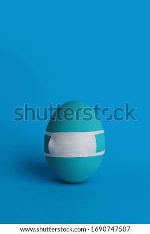Monochrome Easter quarantine concept. Blue egg in protective medical mask on blue background. Stop coronavirus. Easter 2020. Egg close up. Be safe- wear mask. Easter egg in mask  #1690747507