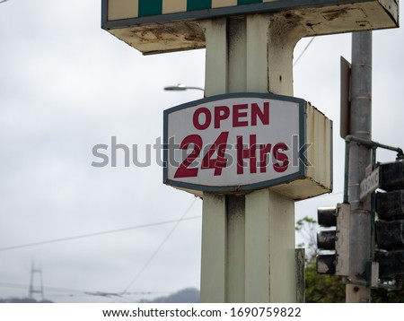 Open 24 hours sign hanging on store billboard sign outside a shopping center #1690759822