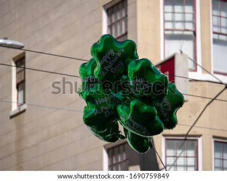 Festive happy St Patrick s Day green shamrock balloons floating in an urban setting #1690759849