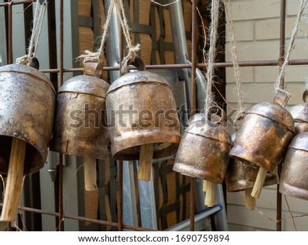 Lantern gong style bells hanging by string on wall on display #1690759894