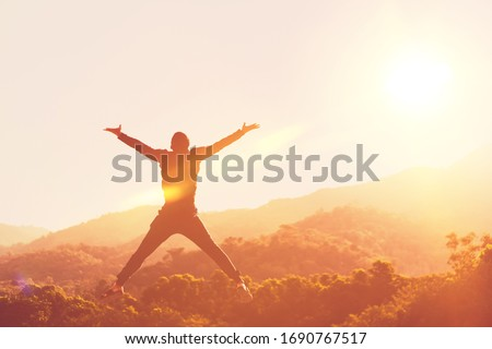 Happy man jumping at top of mountain with sunset sky abstract background. Freedom feel good and summer vacation concept. Vintage tone filter effect color style. Royalty-Free Stock Photo #1690767517