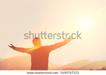 Copy space of man hand raising on top of mountain and sunset sky abstract background. Freedom travel adventure and business victory concept. Vintage tone filter effect color style. Royalty-Free Stock Photo #1690767523