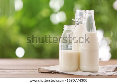 Bottles of fresh milk on table outdoors Royalty-Free Stock Photo #1690774300