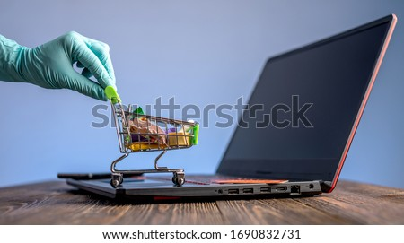 A hand in a sterile medical glove holds a shopping cart with a credit card for online purchases. Concept of internet purchasing important life support products during the coronavirus pandemic #1690832731