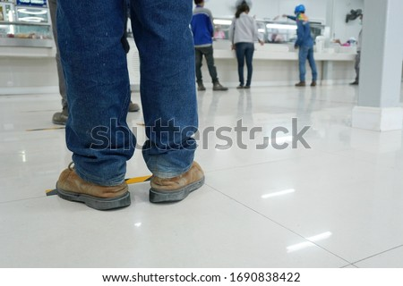 Worker stands before the yellow-black line up to wait to buy food in the factory canteen room during corona virus epidemic. (Covid 19) #1690838422