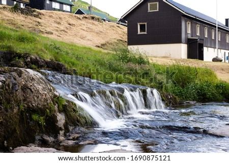Picturescue view of water streaming from the hill with the brown wooden house at the background. Rural life. Summer in mountain village. Social distance. #1690875121