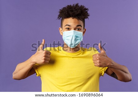 Covid19, healtcare and medicine concept. Enthusiastic happy spanish guy in facial mask, show thumbs-up and smiling with eyes, excited, support social-distancing, prepared for going grocery shopping #1690896064