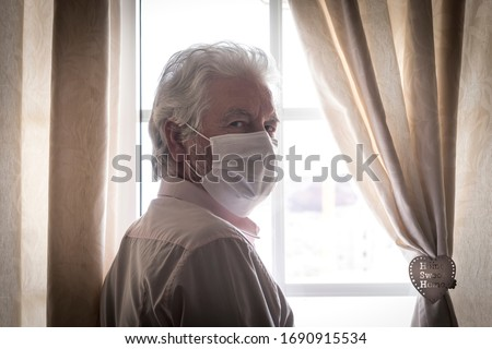 Coronavirus quarantine. Senior man wearing protective mask behind the window stay at home to avoid contagion by COVID-19 - responsibility and prevention concept Royalty-Free Stock Photo #1690915534
