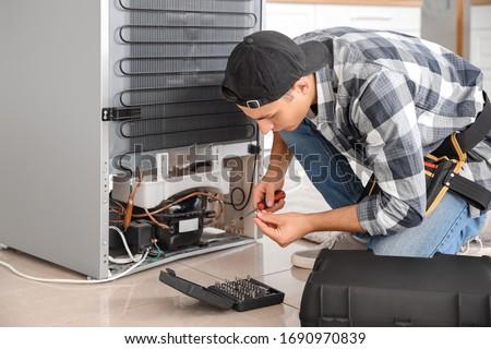 Worker repairing refrigerator in kitchen Royalty-Free Stock Photo #1690970839