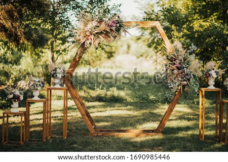 Wedding wooden arch in rustic style decorated with grass hay field color and flowers. Near wooden boxes with flower bouquets. Wooden arch and flower decoration. Wedding ceremony in sunny summer day. Royalty-Free Stock Photo #1690985446