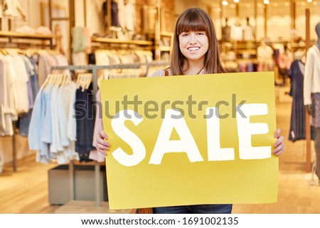 Young woman holding sale sign in retail in mall #1691002135