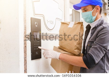 Courier in protective mask and medical gloves delivers takeaway food. Delivery service under quarantine, disease outbreak, coronavirus covid-19 pandemic conditions. #1691016106