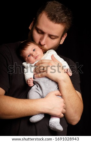 Studio portrait of handsome muscular man in black t-short holding on hands cute little baby over black background with copyspace. Family, love and happiness concept. #1691028943