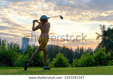 Golfer sport course golf ball fairway.  People lifestyle woman playing game golf tee of on the green grass sunset background.  Asia female player game shot in summer.  Healthy and Sport outdoor #1691045347