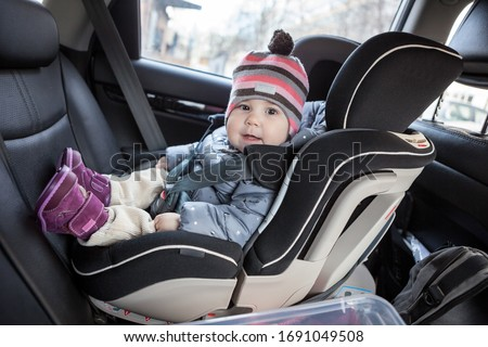 Child safety seat with smiling infant child is on back seat of car, a kid eight month old Royalty-Free Stock Photo #1691049508
