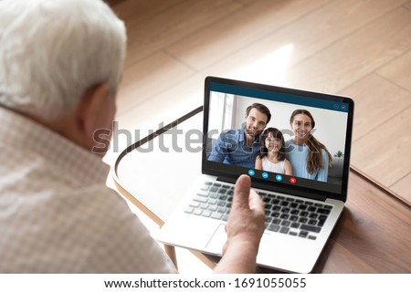 Back view of elderly grandfather talk chat on video call on computer with family and granddaughter, mature granddad have online conversation using webcam on laptop with happy relatives #1691055055