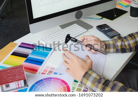Engineers and creative artists work on table, work, consult, advise on choosing colors and materials, measuring size, choosing cool colors, soft tones, beautiful tones.