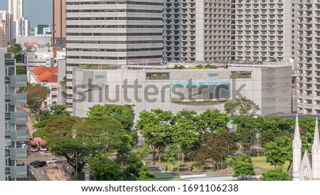 Skyscrapers near St. Andrew's Cathedral aerial timelapse. It is an Anglican cathedral in Singapore, the country's largest cathedral. Green trees and park, traffic on a street