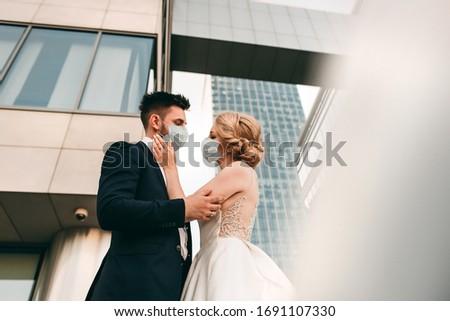 Young loving brides walking in modern city medical masks during quarantine on their wedding day. Coronavirus, disease, protection, sick, illness flu europe celebration canceled, surgical protective #1691107330