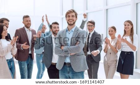 smiling entrepreneur on the background of jubilant business team #1691141407